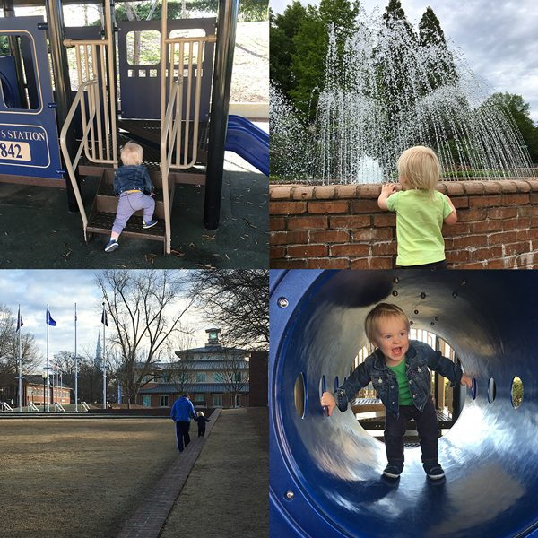 Toddler playing at train, field, and fountain at Smyrna Library