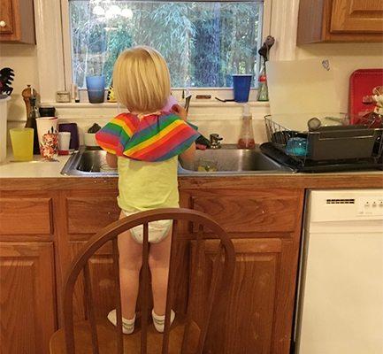 Toddler washing dishes.