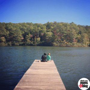 kids sitting on dock on mountain lake