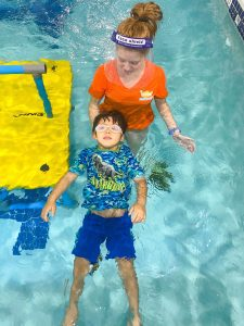 Goldfish Swim School instructor guides a student with his back float.